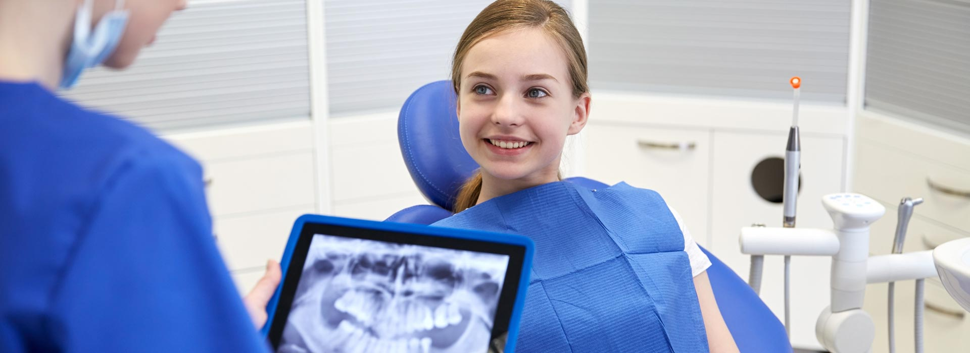 Dental assistant showing digital X-rays to patient